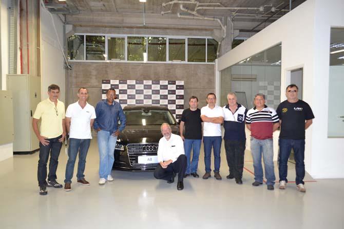Os consultores automotivos da revista Farol Alto-100% Motor e o consultor técnico da Audi, Lothar Werninghaus (agachado)